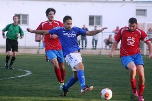 Adri trata de llegar a un balón entre dos rivales