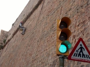 Un trabajador realiza trabajos de mejora en la muralla suspendido de la misma con un arnés