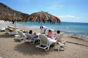 Varios turistas extranjeros se relajan mientras un camarero les sirve la comida junto al mar.