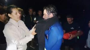 Beatriz Santos, su pareja, le ayuda a ponerse un jersey para protegerse del frío.