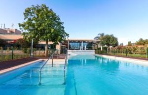 La piscina exterior de Sa Residència con los apartamentos en venta al fondo.
